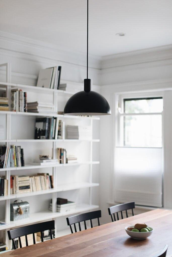 minimalist dining room with modern bookshelves, black pendant light and white cellular shades on windows