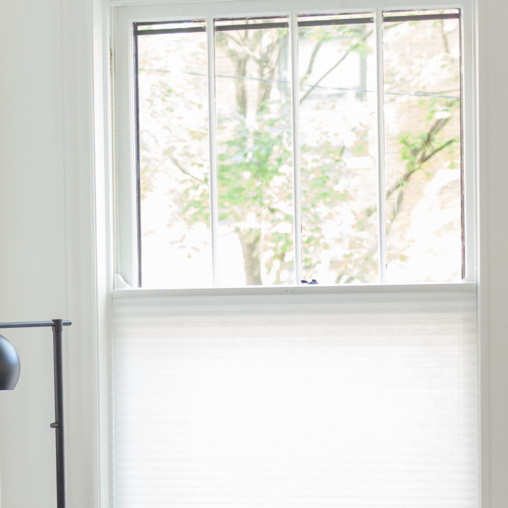 closeup of window with white top down cell shades