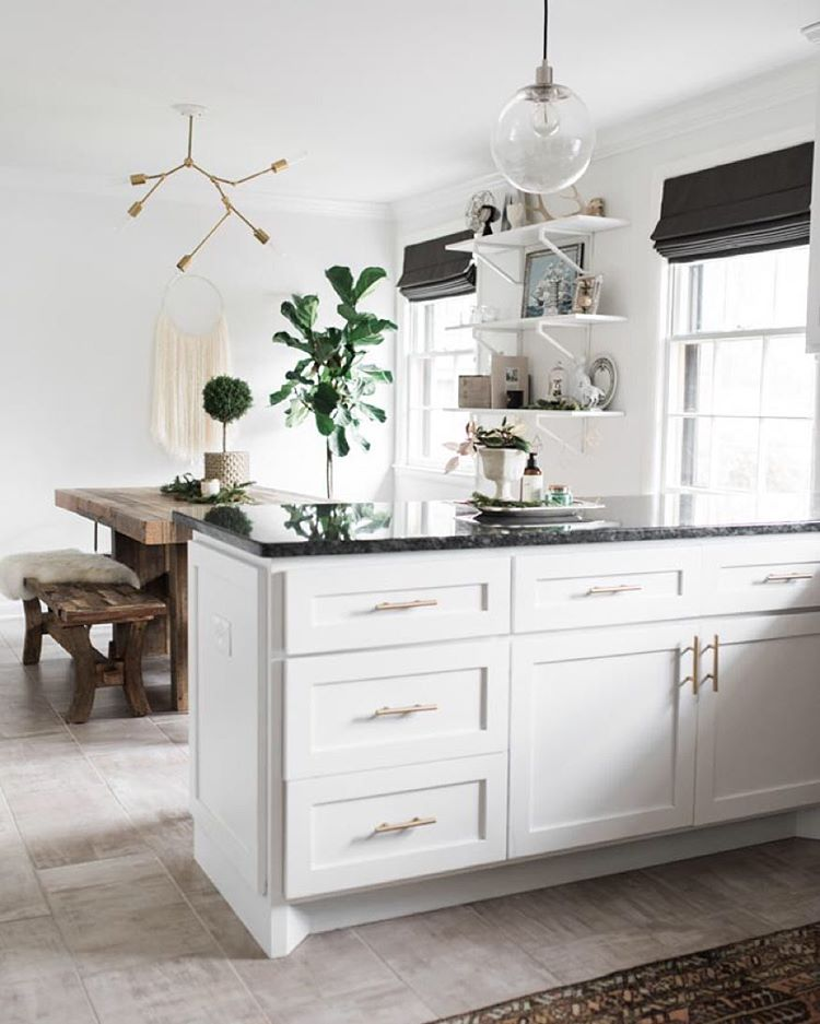 modern kitchen with white cabinets, dark countertops and black roman shades