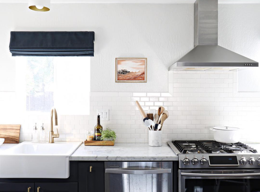 kitchen with no upper cabinets, stainless steel vent hood and navy roman shade on window over sink