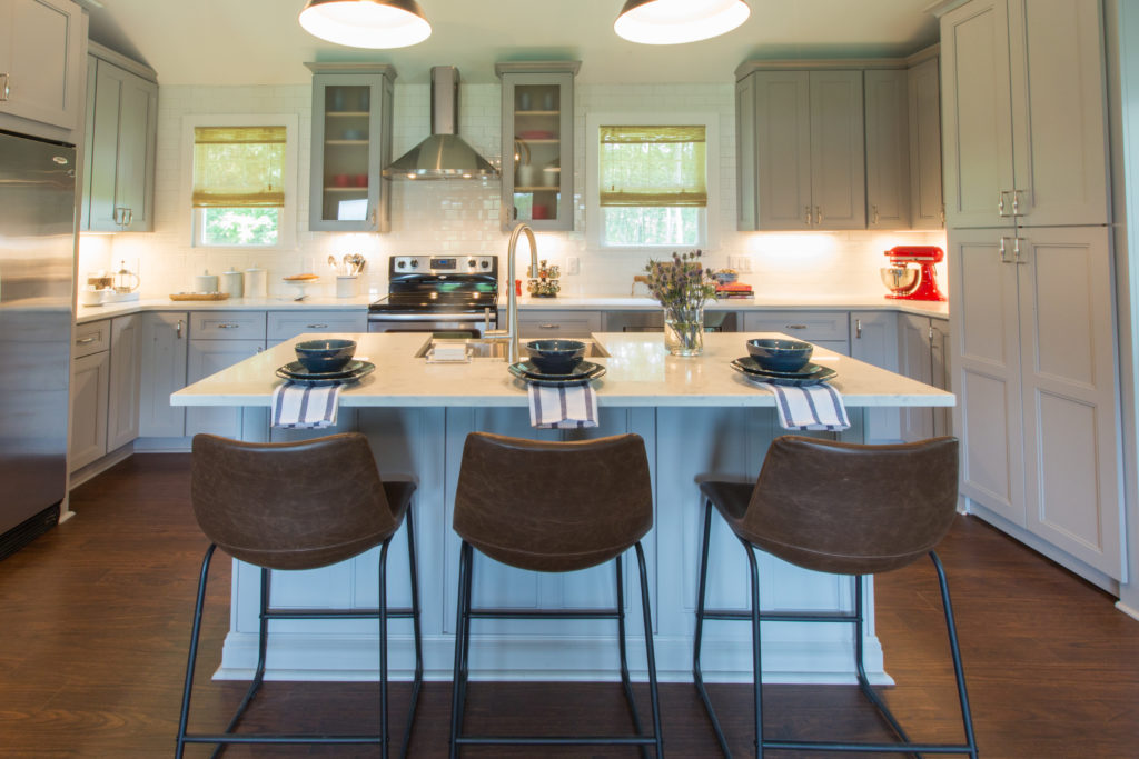eclectic kitchen with leather barstools, large island, grey cabinets and sheer bamboo shades on windows