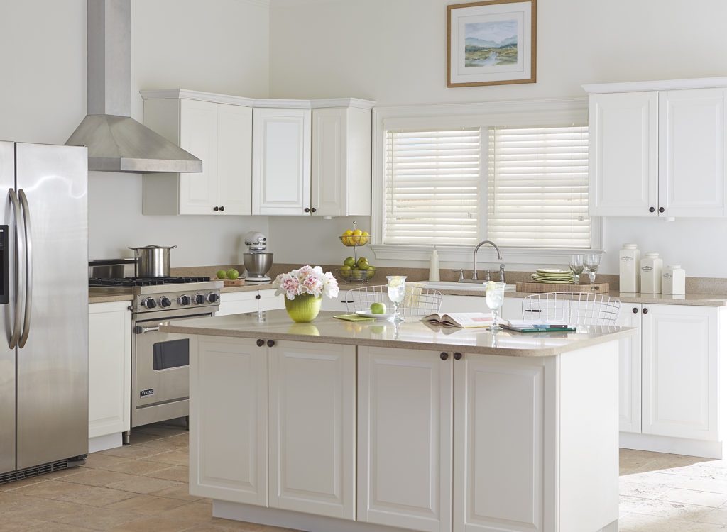 traditional white kitchen with island and white faux wood blinds on window over sink