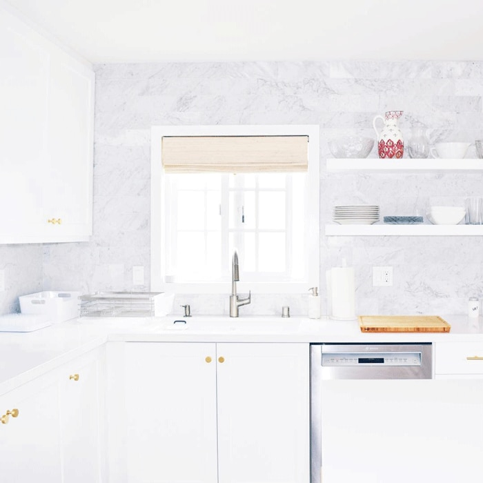 Bright white kitchen with gold cabinet hardware, marble backsplash to the ceiling and woven wood shade on window behind sink