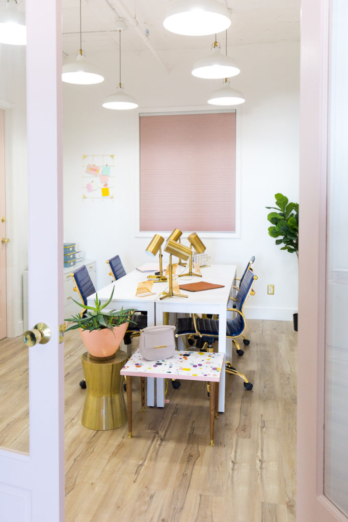 Shared office space with white table, gold desk lamps, pink french doors and pink cellular shades on windows