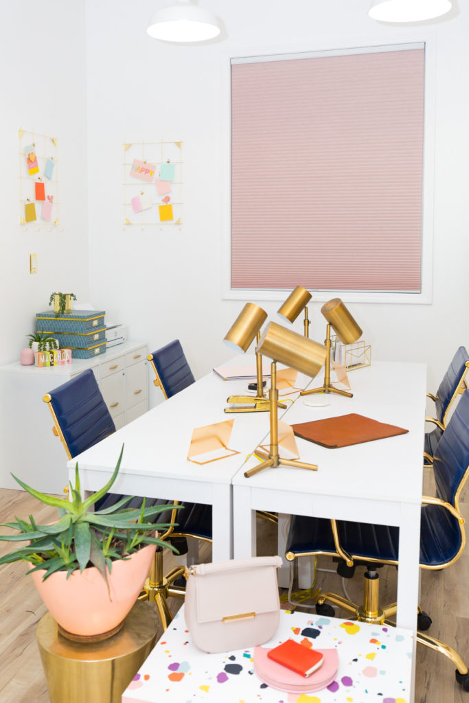 Office with shared white desk, white walls, gold accessories and pink cellular shades