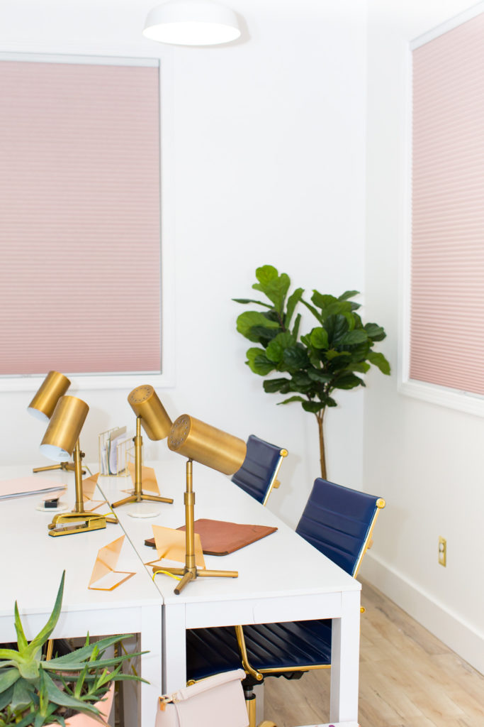 Modern office with fiddle leaf fig tree, navy blue leather desk chairs and blush pink window shades