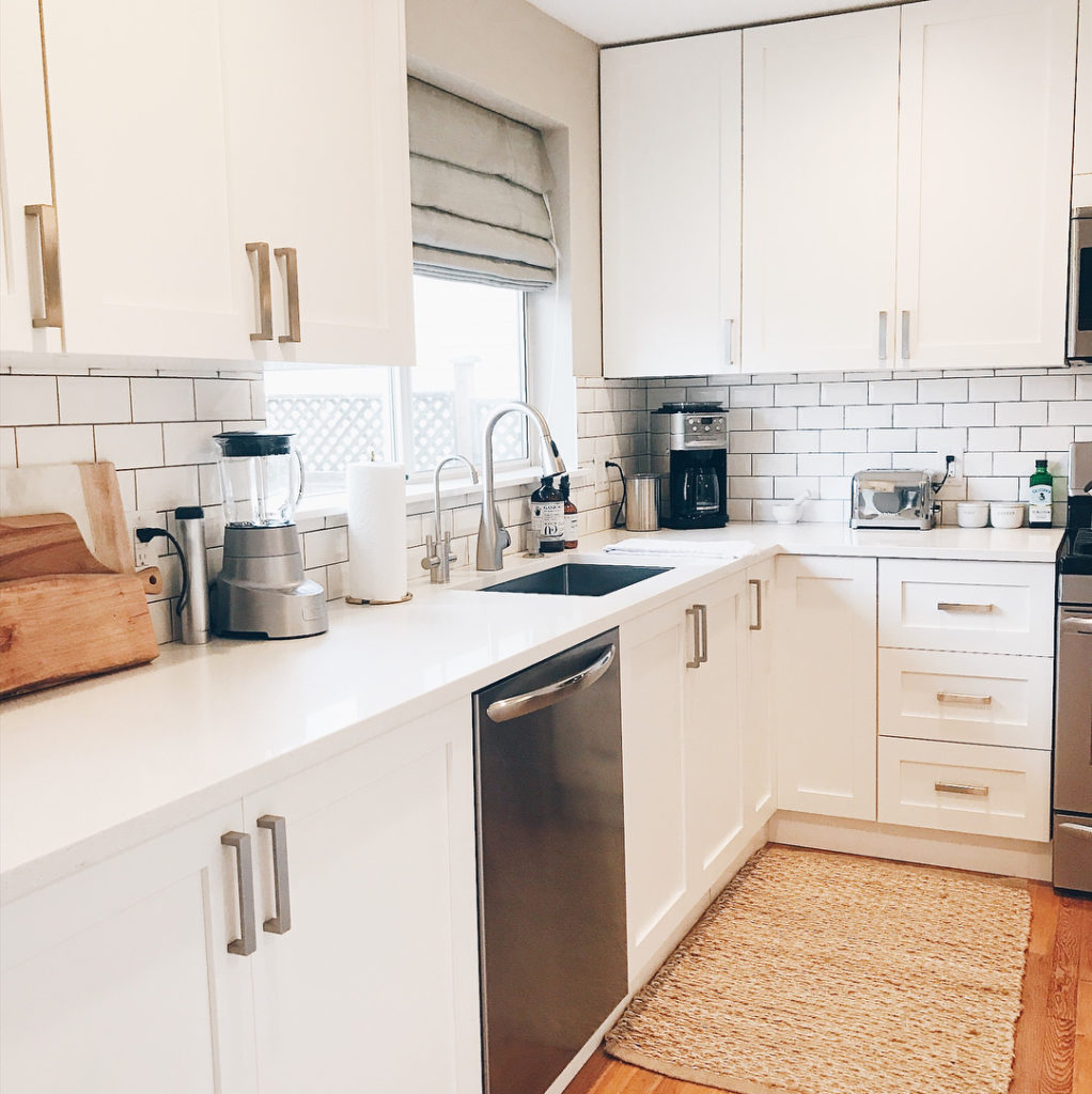White kitchen with shaker style cabinets, stainless steel appliances and grey roman shade on wide window over sink