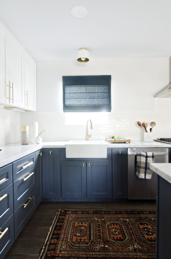 navy and white kitchen with turkish rug, modern farmhouse sink and navy blue roman shade