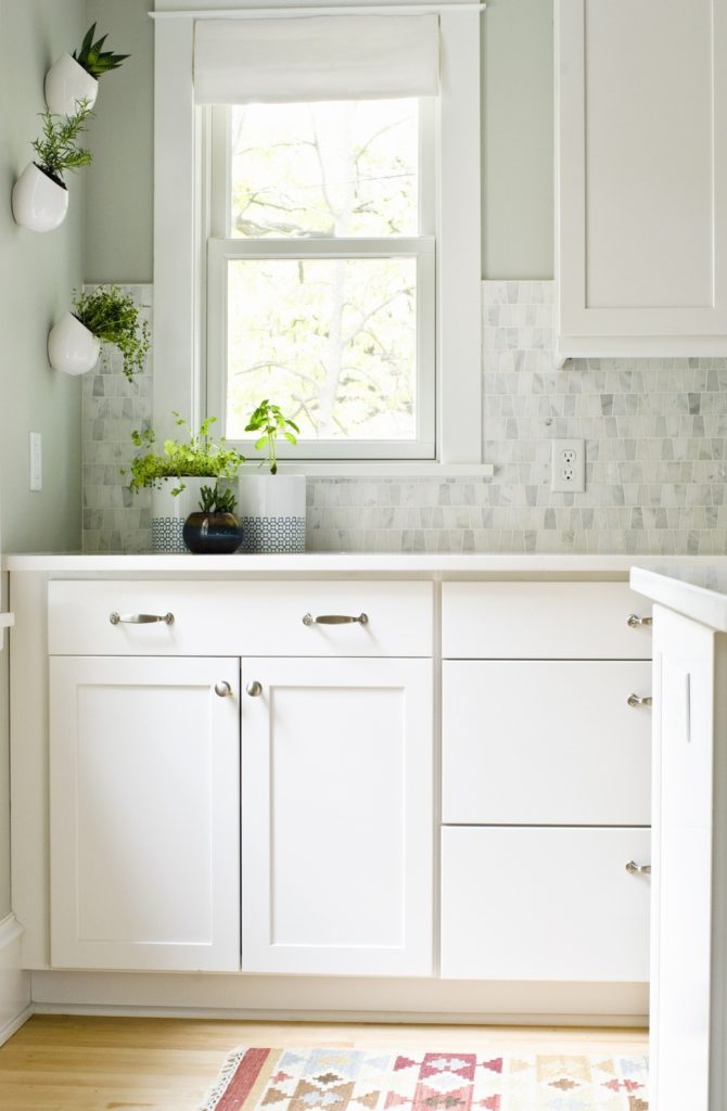 White kitchen with stainless steel hardware, marble mosaic backsplash and white fabric roman shade on window